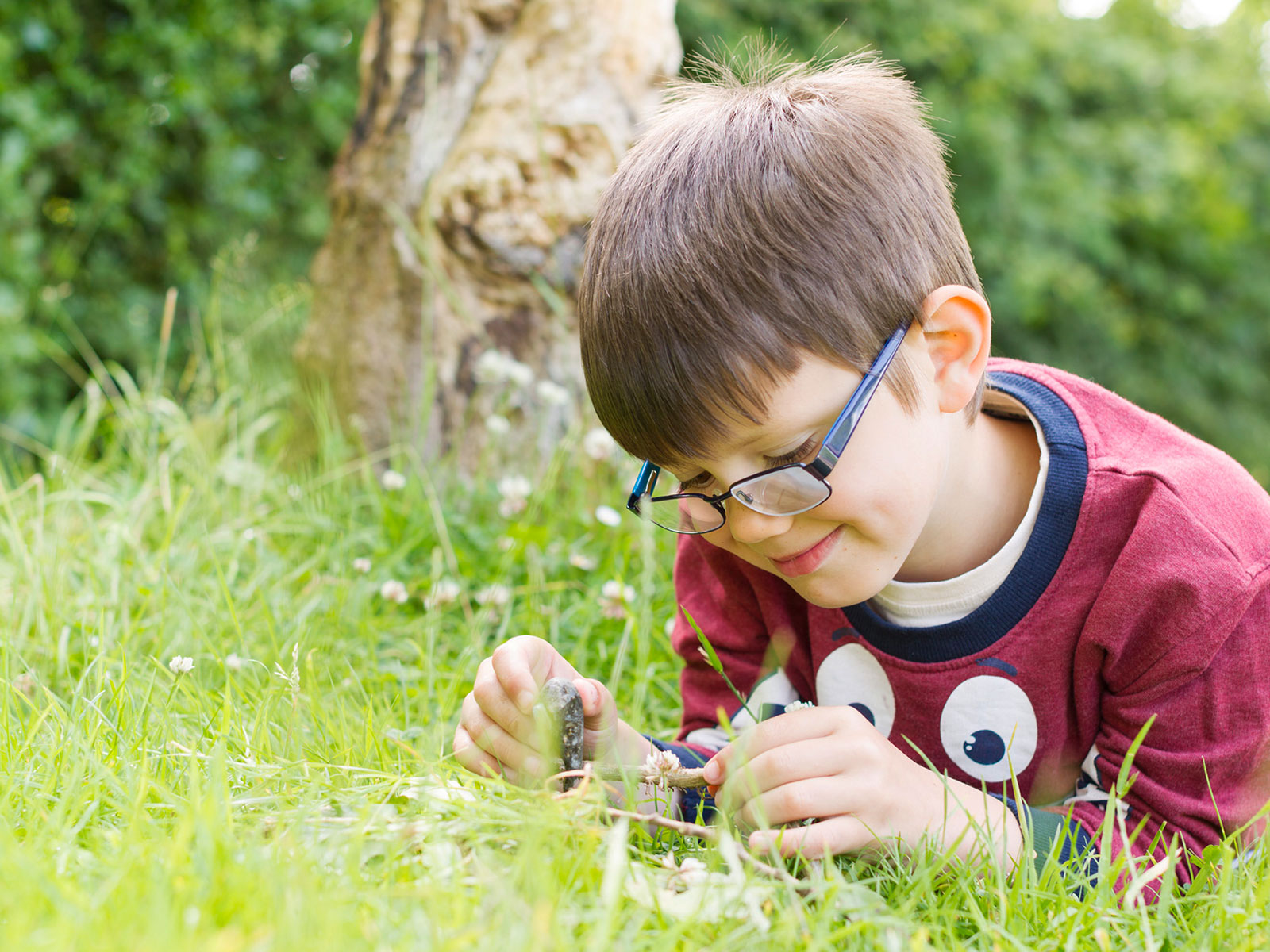 COMBS infant school photography boy lying on the grass smiling at sticks